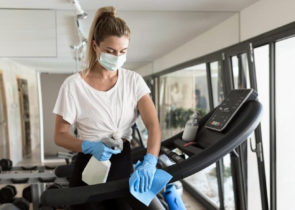 mulher limpando equipamento de academia
